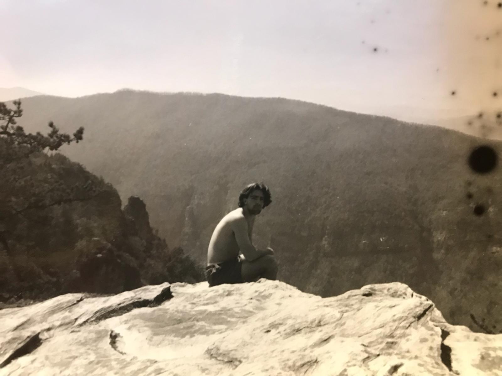 Ryan C. Hurst Shirtless perched on a mountain edge